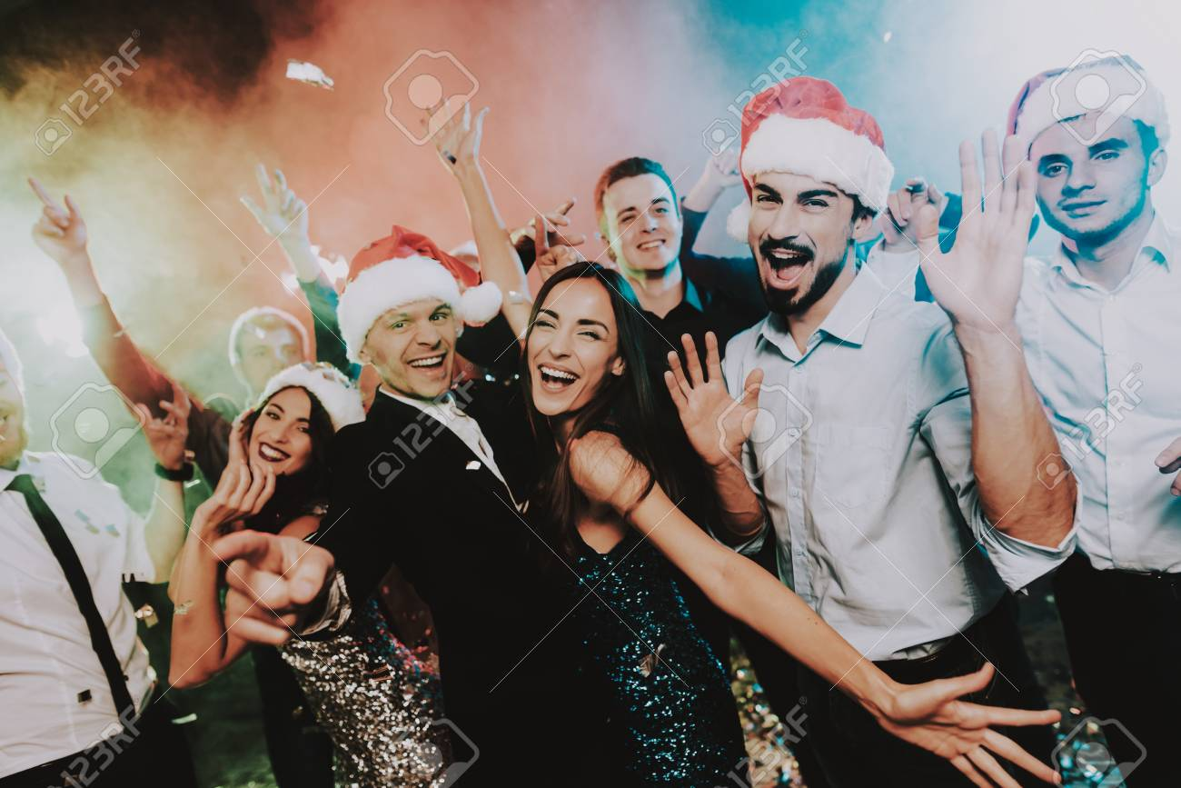 People in Santa Claus Cap Celebrating New Year. Happy New Year. People Have Fun. Indoor Party. Celebrating of New Year. Young Woman in Dress. Young Man in Suit. Happy People. Red Cap. - 109914217