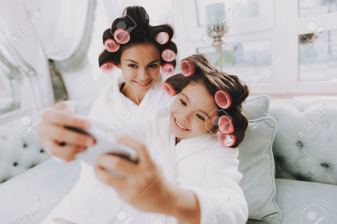 Little Lady with Curlers. Mother and Daughter in Spa. Consept Beauty Salon. Smiling Mother and Girl. Beautiful Face. Woman and Happy Child. Woman with Curlers. Doing Selfie. Blue Sofa in Spa Salon. - 110087877
