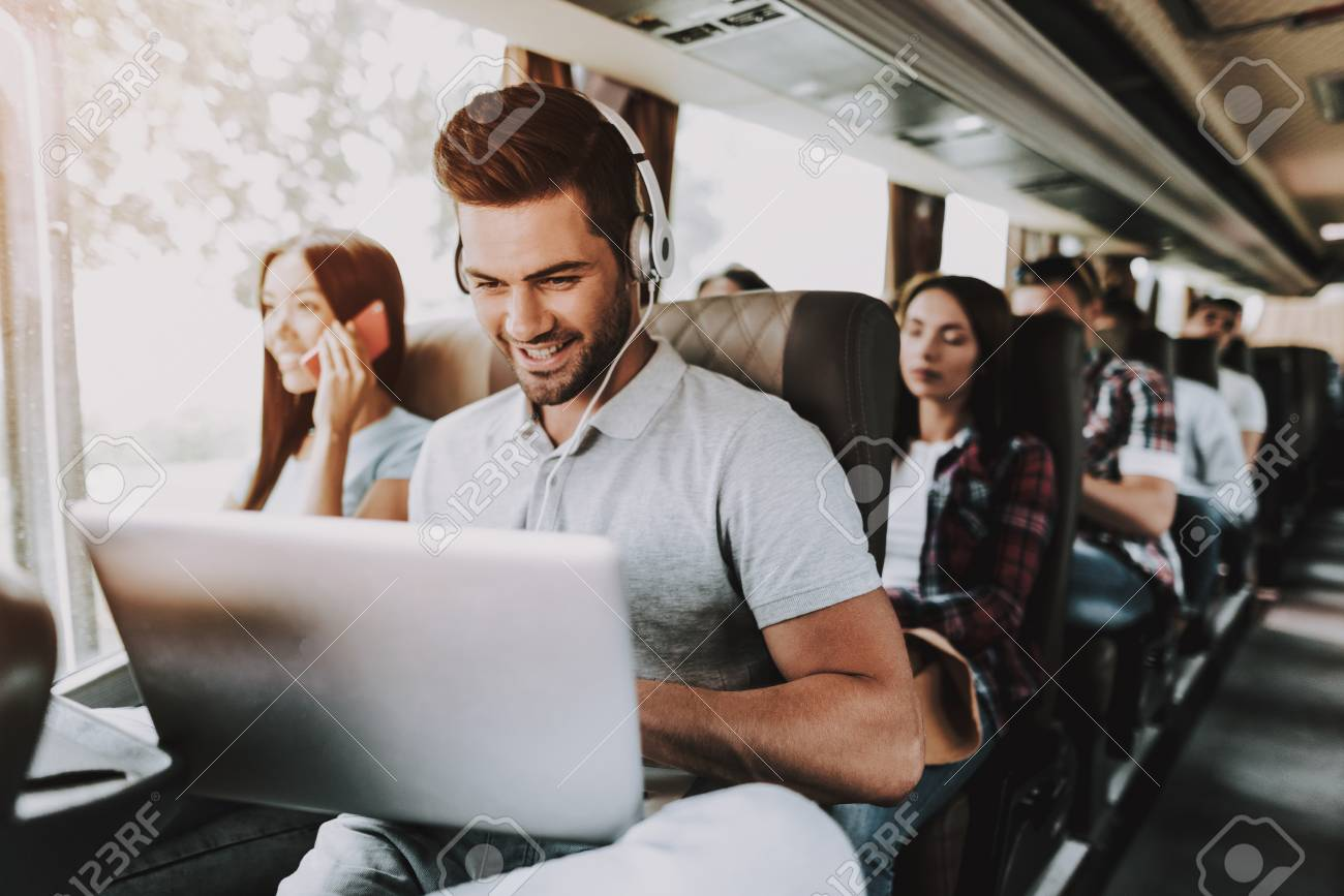 Smiling Man in Headphones Using Laptop in Tour Bus. Young Handsome Man Sitting on Passenger Seat of Tourist Bus and Typing on Laptop. Traveling and Tourism Concept. Happy Travelers on Trip - 111173818