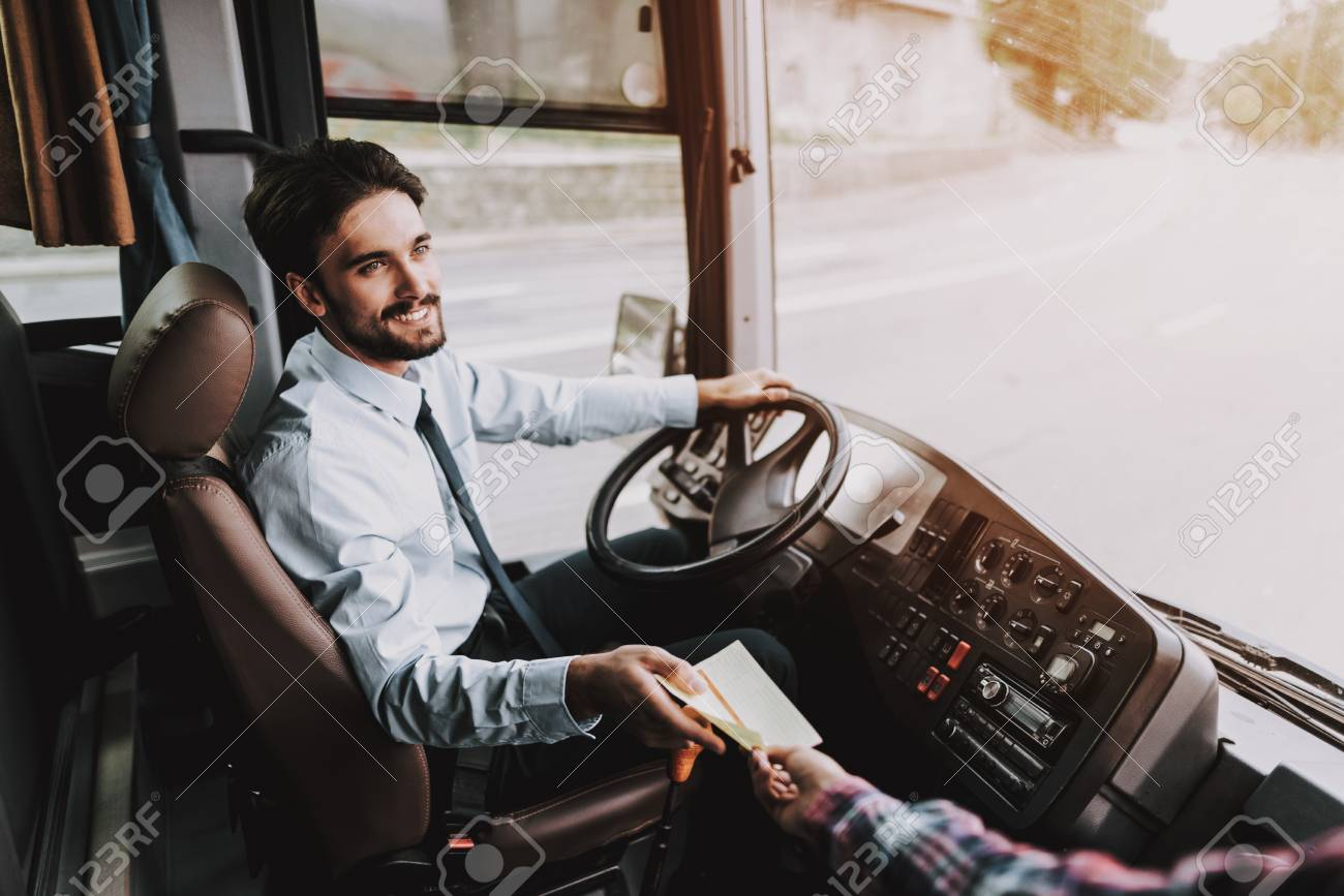 Smiling Young Driver taking Ticket from Passenger. Handsome Happy Man wearing Blue Shirt Sitting on Driver Seat of Tour Bus. Attractive Confident Man at Work. Traveling, Transport and Tourism Concept - 111177421