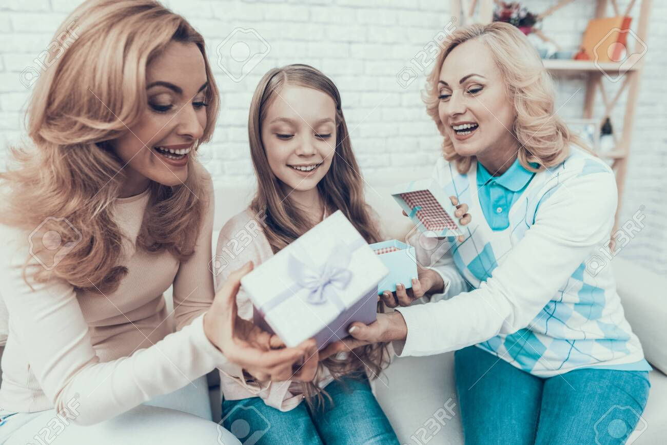 Grandmother Giving Gift Boxes to Family at Home. Mother with Daughter. Smiling Women. Celebration Concept. Happy Family. Sitting at Home. Holiday in March. White Sofa. Happy Daughter. - 135014386