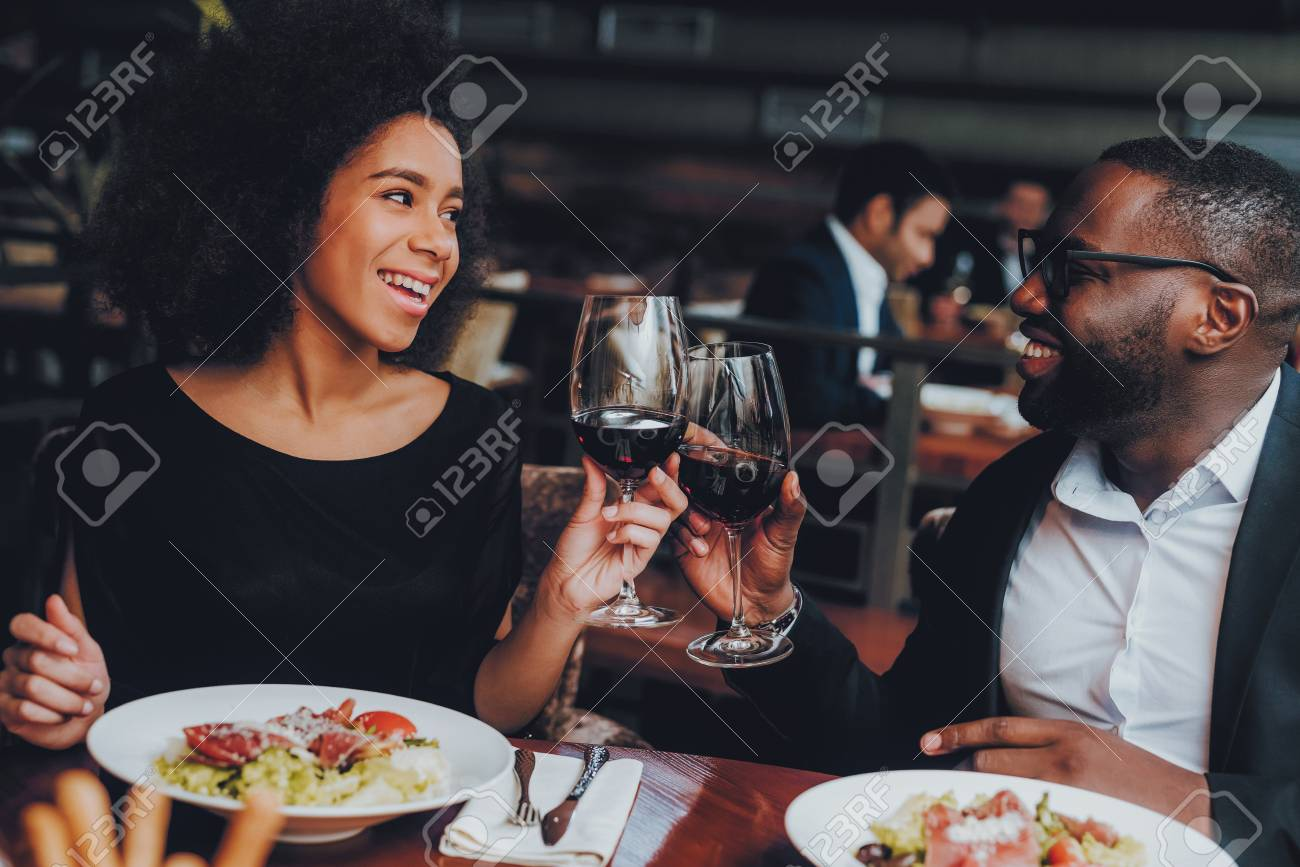 African American Couple Dating in Restaurant. Romantic Couple in Love Dating. Cheerful Man and Woman with Menu in a Restaurant Making Order. Romantic Concept. Cheers Classes Red Wine. - 113607805