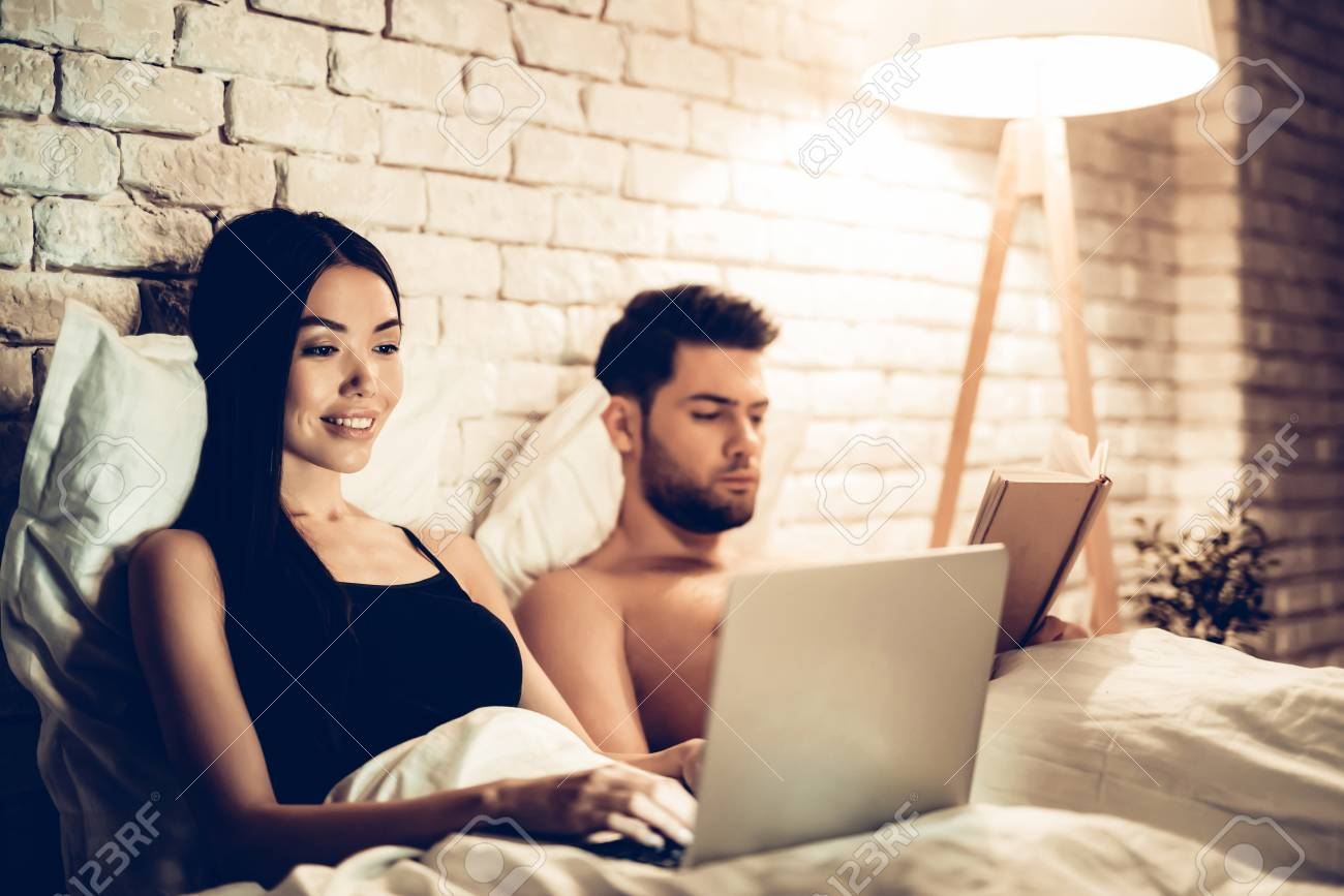 Couple Using Laptop Reading Book Before Sleeping. Young Guy Watching Movie or Browsing Internet. Girl Reading Book at Night. Relationship Concept. Wife and Husband. - 113961727