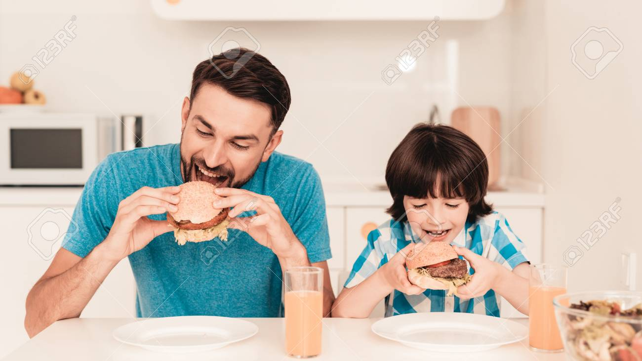 Smiling Son and Father Have Lunch in Kitchen. Boy in Shirt. Modern Kitchen. Sitting Boy. Boy with Spoon. Breakfast in Morning. White Table in Kitchen. Burger in Hands. Young Father. - 115669036