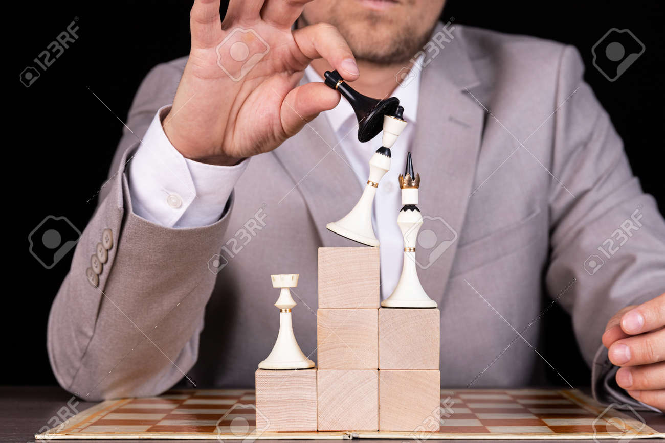 A businessman is building a pyramid of chess pieces and wooden blocks. The concept of construction, growth, development, success. - 148773686