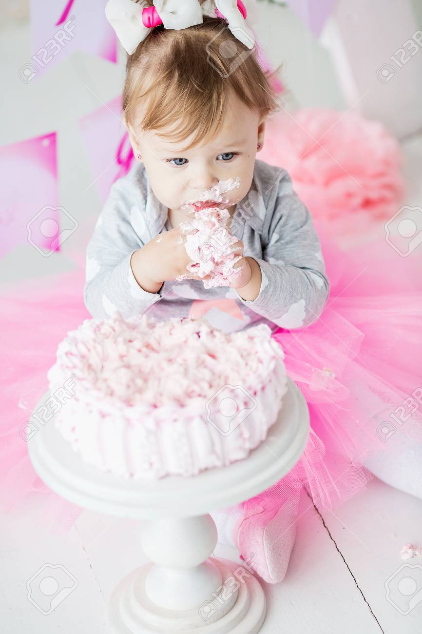 Baby Girl 1 Year Old Celebrating First Birthday In Room Eating Cake Decoration