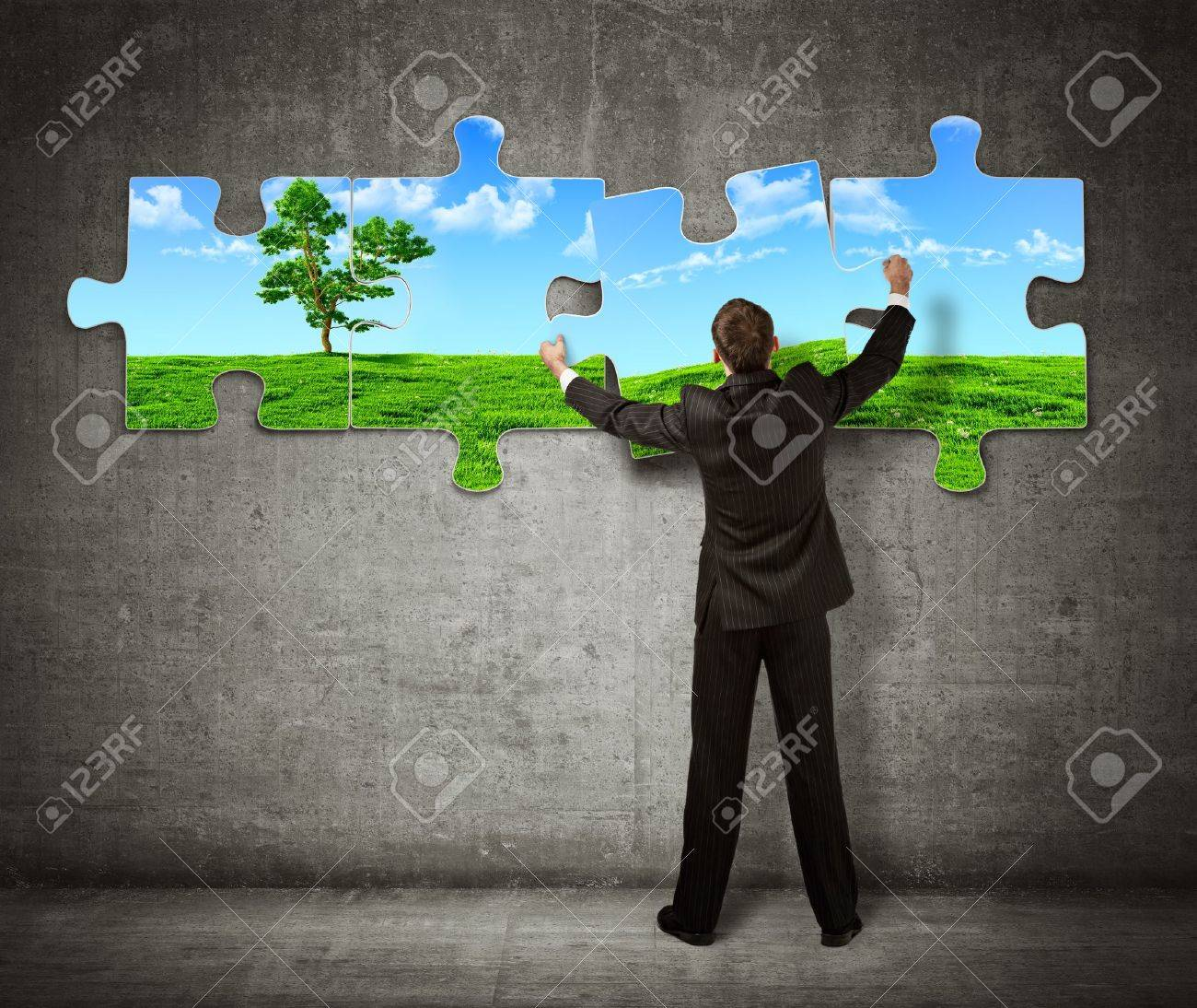 Businessman making a puzzle on the wall with  picture of nature Stock Photo - 16469931