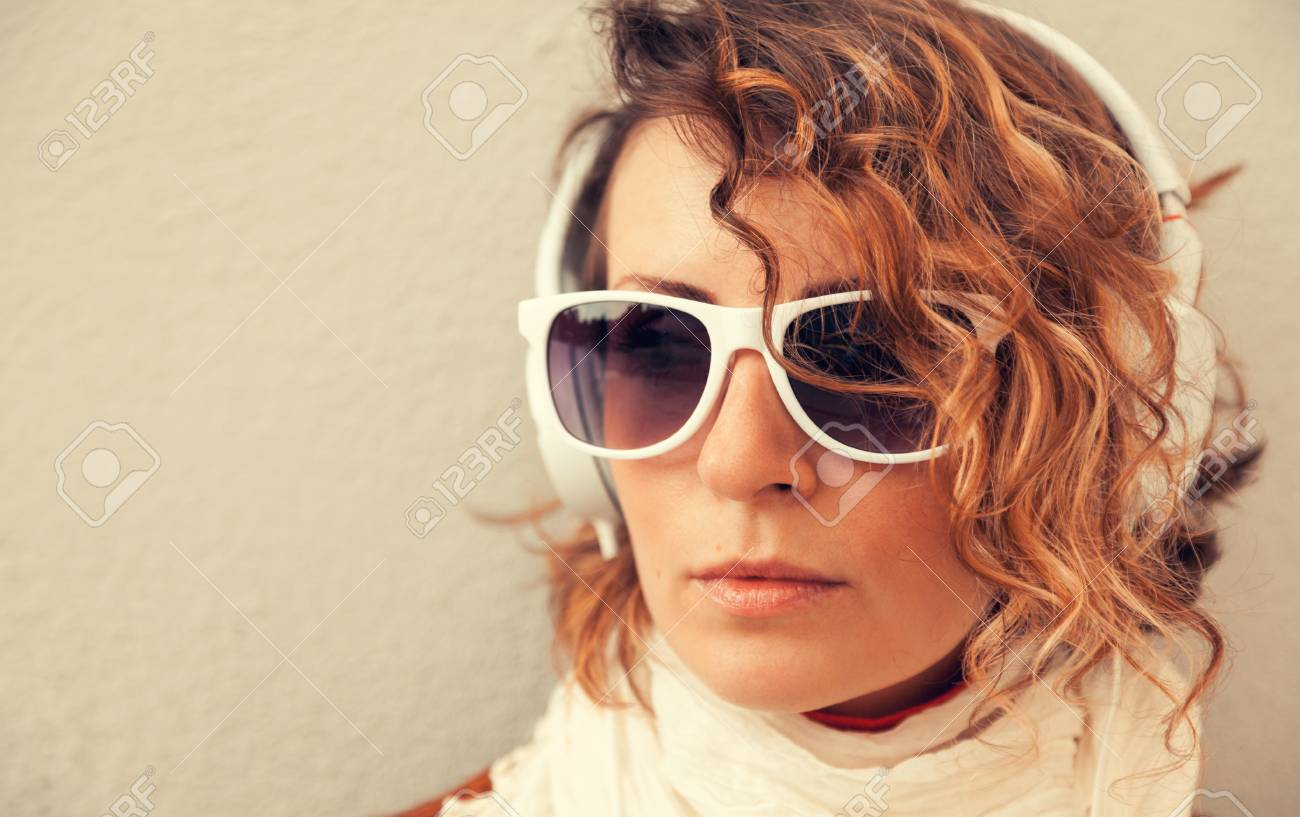 Beautiful young woman in a sunglasses and headphones listening music near the wall Stock Photo - 29425310