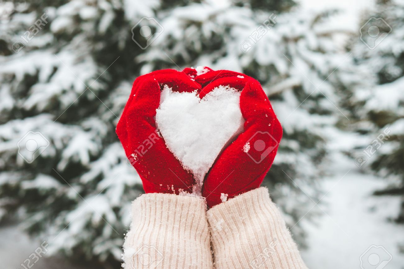 Woman in red gloves holds snow in hands in shape of heart. Stock Photo - 46807305