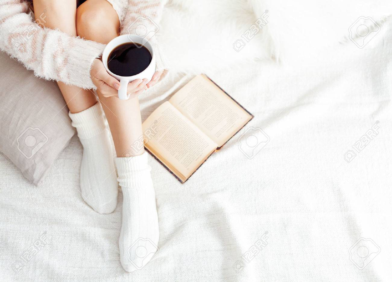 Soft photo of woman on the bed with old book and cup of coffee, top view point Stock Photo - 49156360