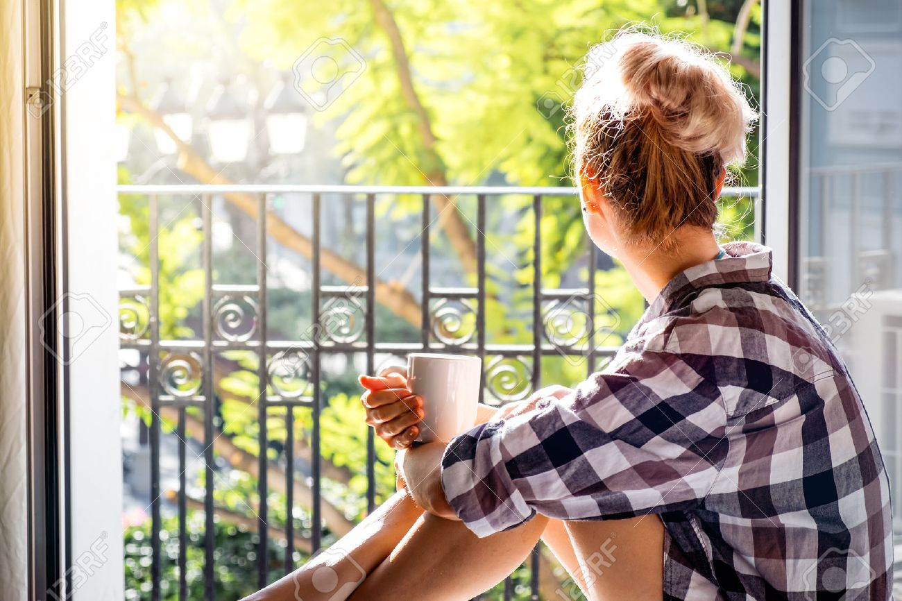 Young pretty woman sitting at opened window drinking coffee and looking outside enjoys of rest - 52650465