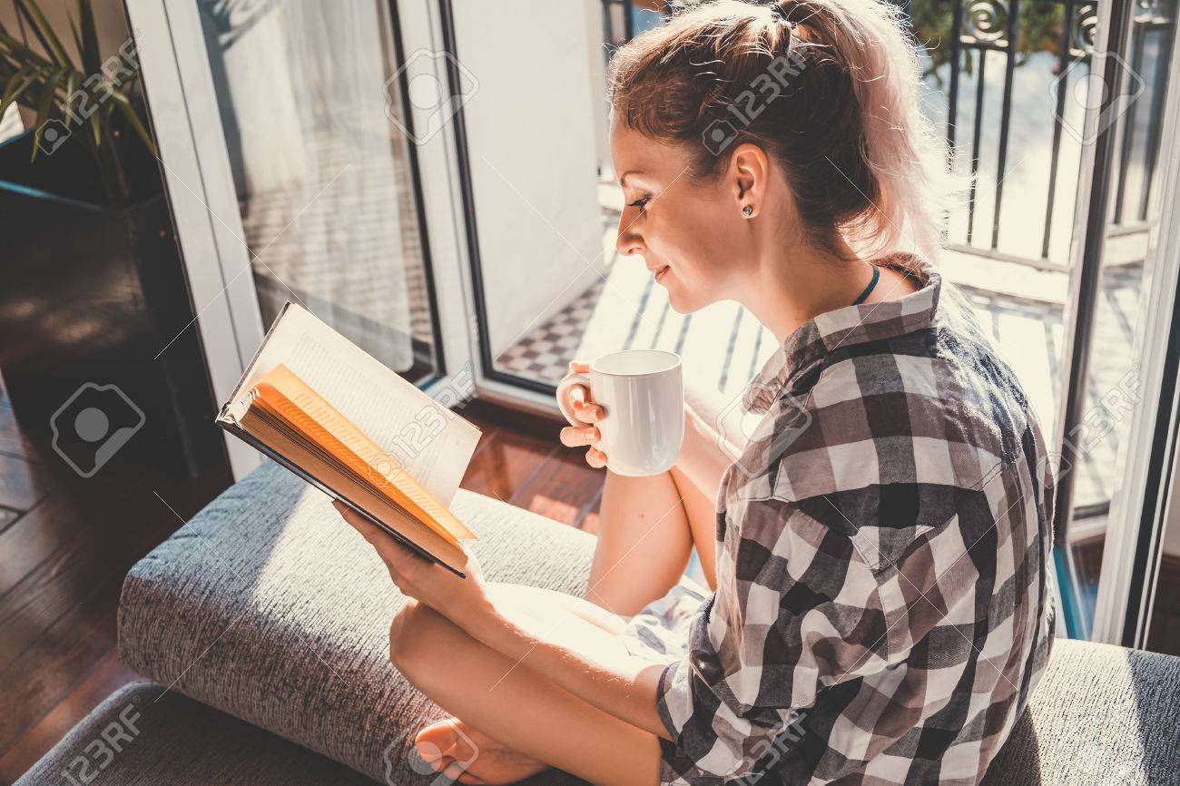 Young pretty woman  sitting at opened window drinking coffee and reading a book enjoys of rest Stock Photo - 52650461