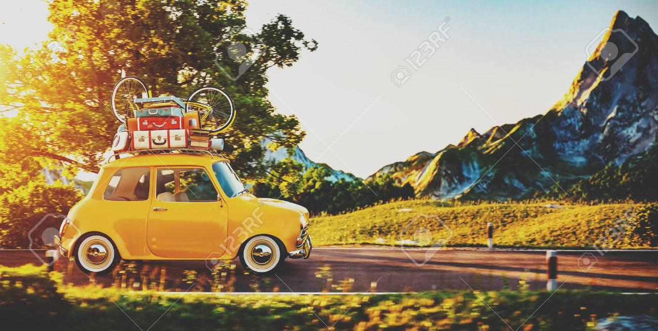 Cute little retro car with suitcases and bicycle on top goes by wonderful countryside road at sunset Stock Photo - 55257471