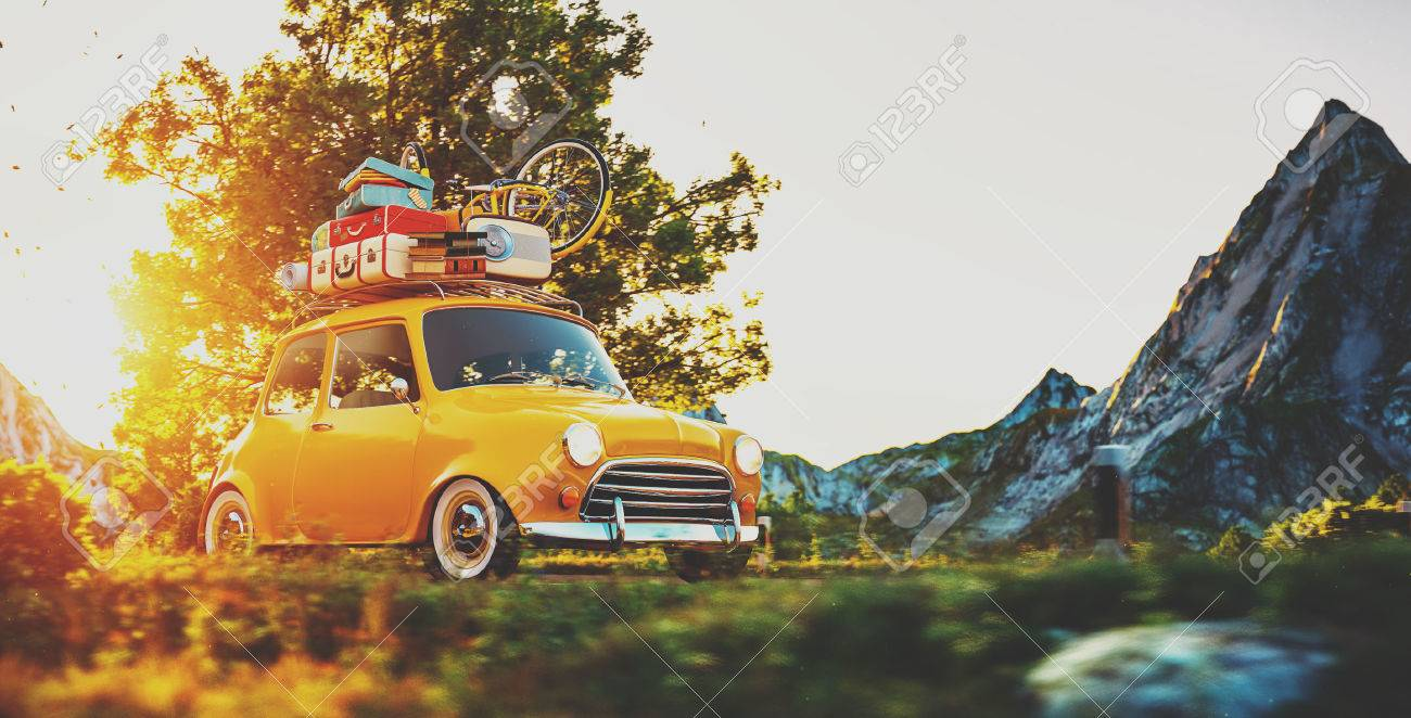 Cute little retro car with suitcases and bicycle on top goes by wonderful countryside road at sunset Stock Photo - 55257477