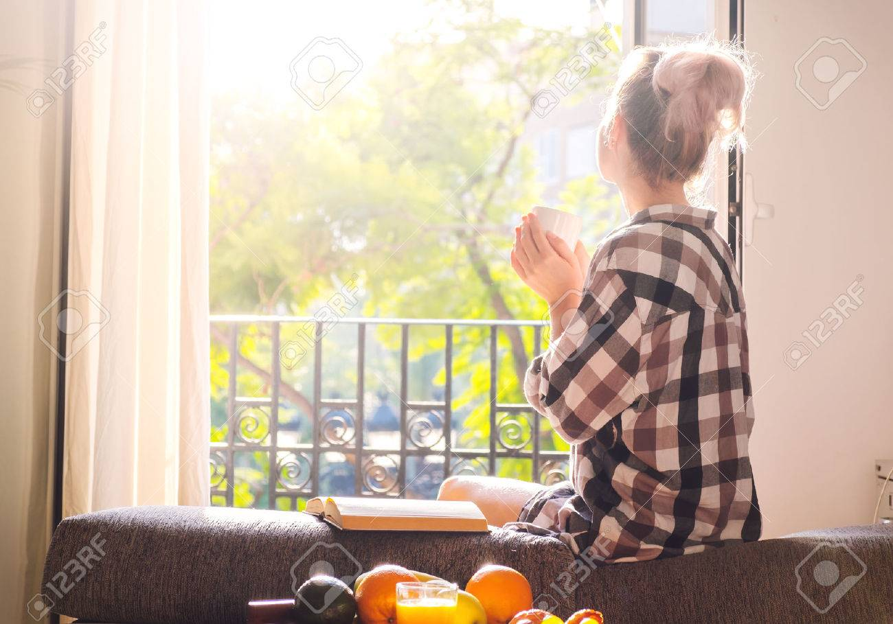 Young pretty woman  sitting at opened window drinking coffee and looking outside enjoys of rest Stock Photo - 55257521
