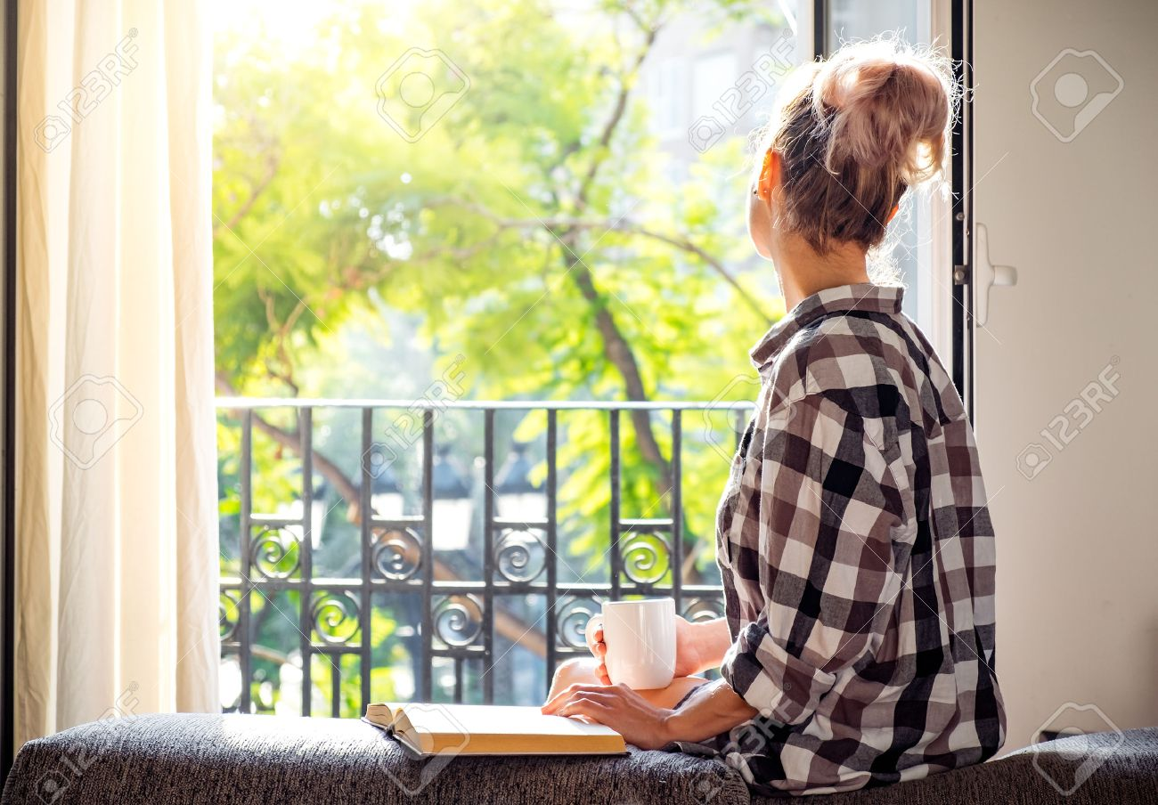 Young pretty woman  sitting at opened window drinking coffee and looking outside enjoys of rest Stock Photo - 58485395