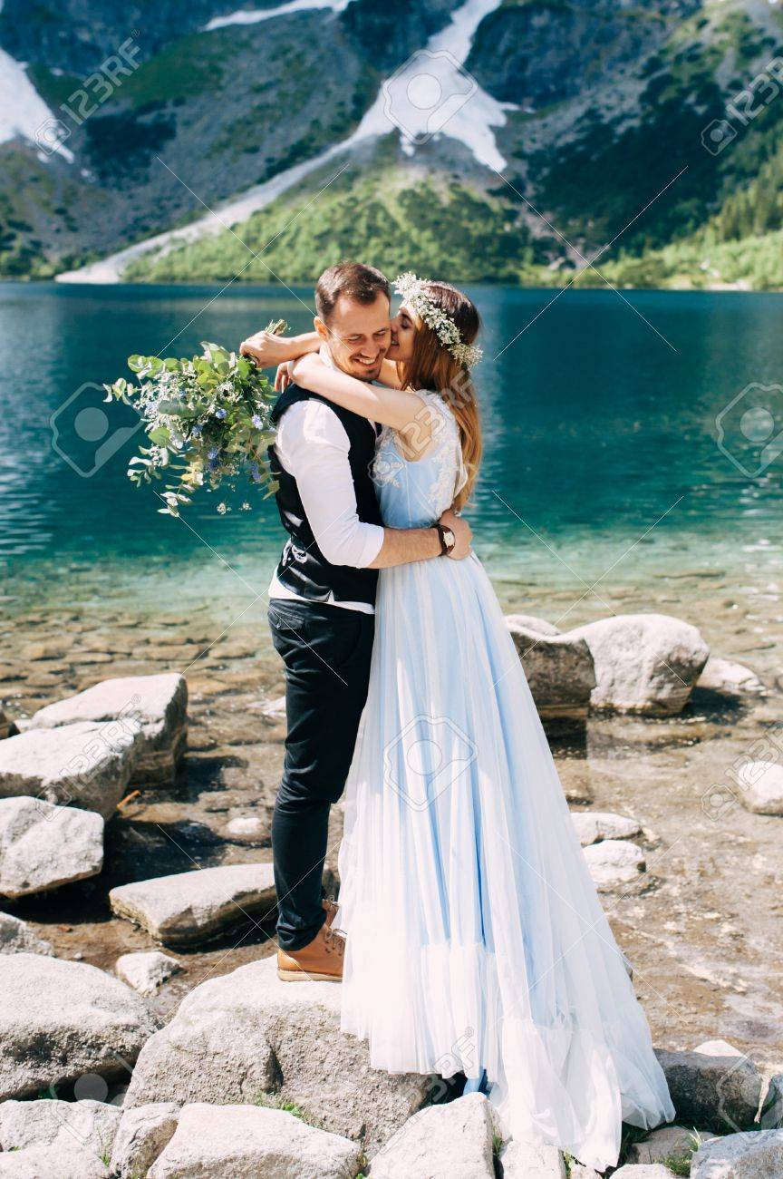 Bride With The Beautiful Blue Dress And Groom Hugging With Views
