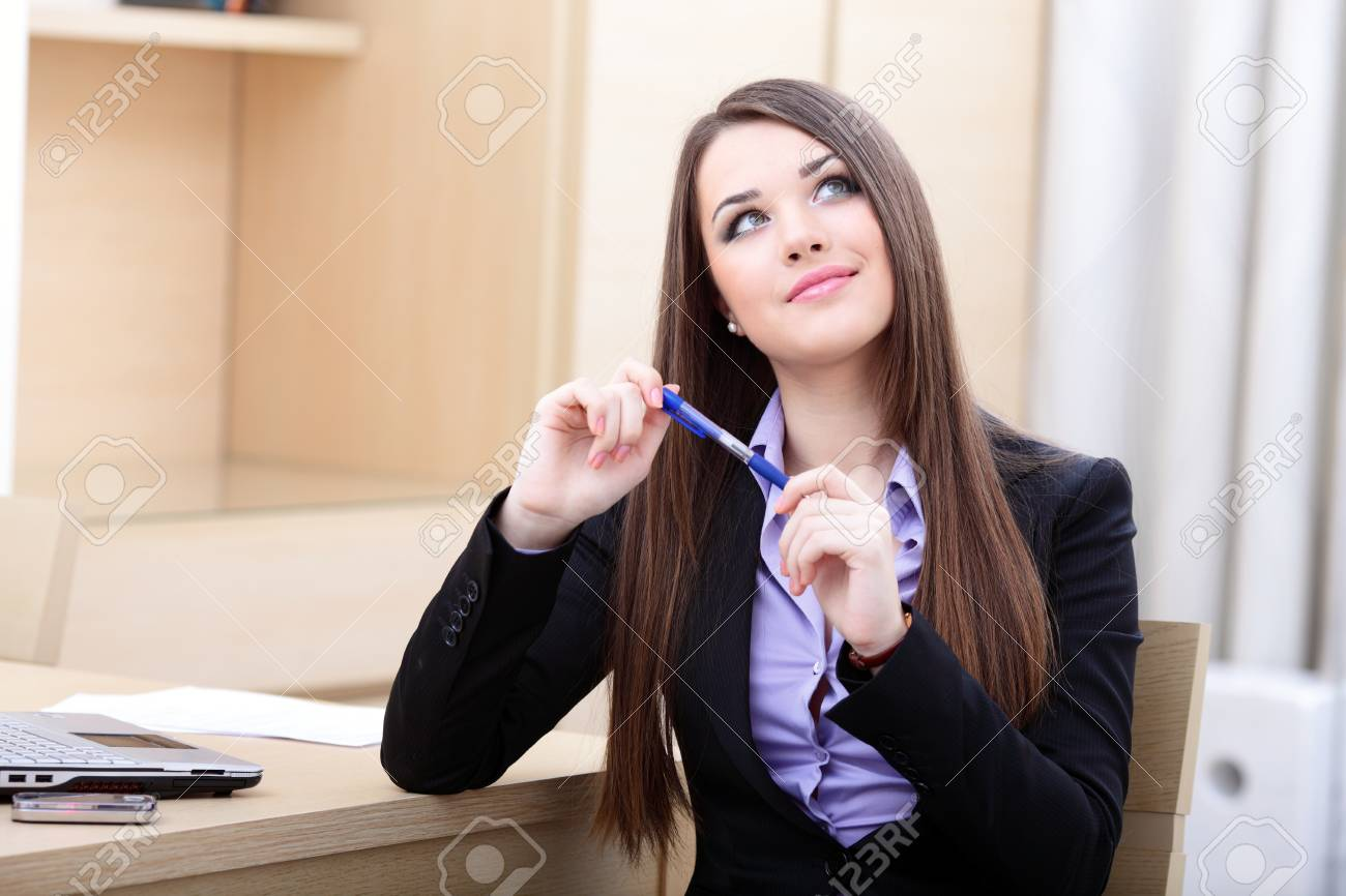 Portrait of a young pensive businesswoman sitting near the table in office Stock Photo - 9365439