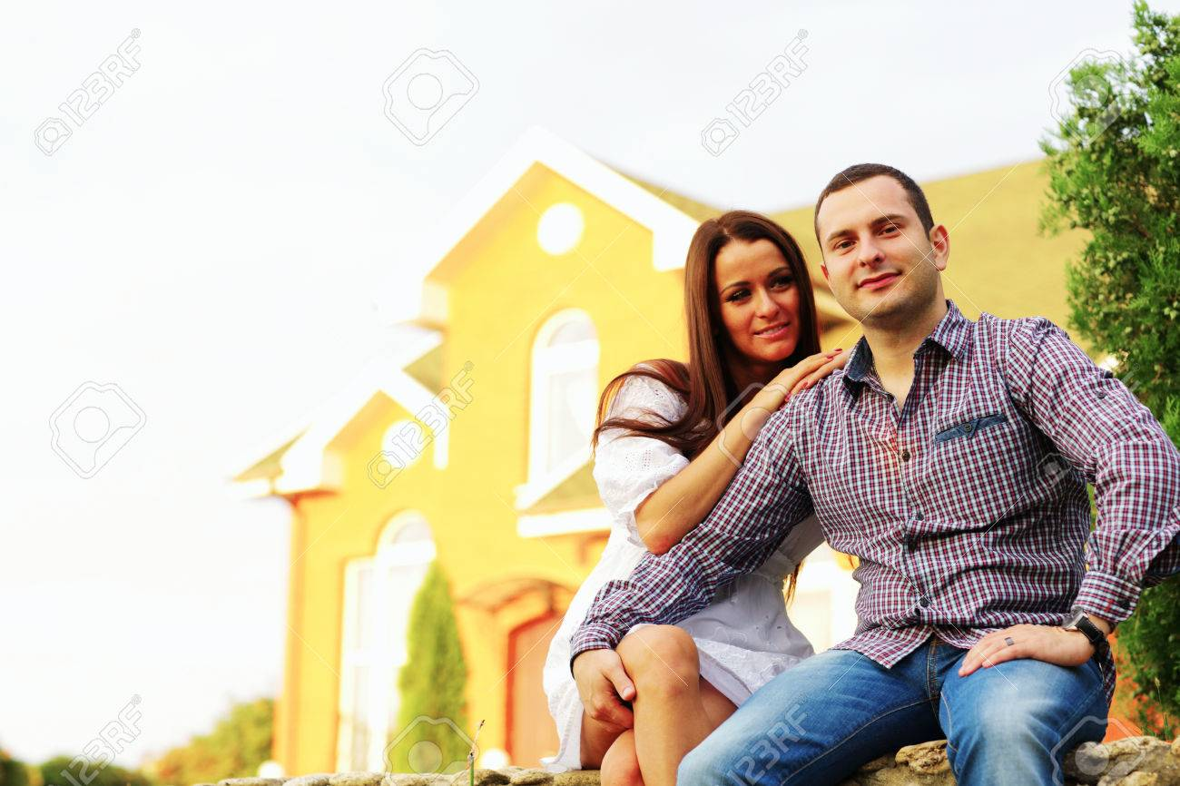 Happy couple sitting in the garden in front of new home Stock Photo - 22573002