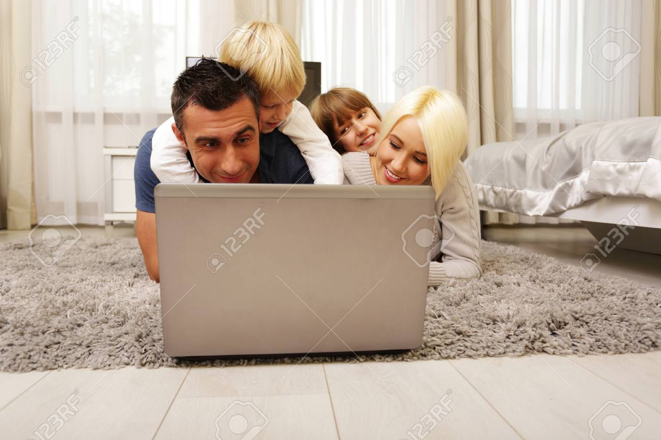 happy family lying on the carpet and playing on a laptop at home Stock Photo - 23993430