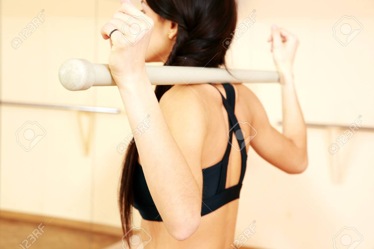 Young fit woman working out with gymnastic stick at gym Stock Photo - 26554827