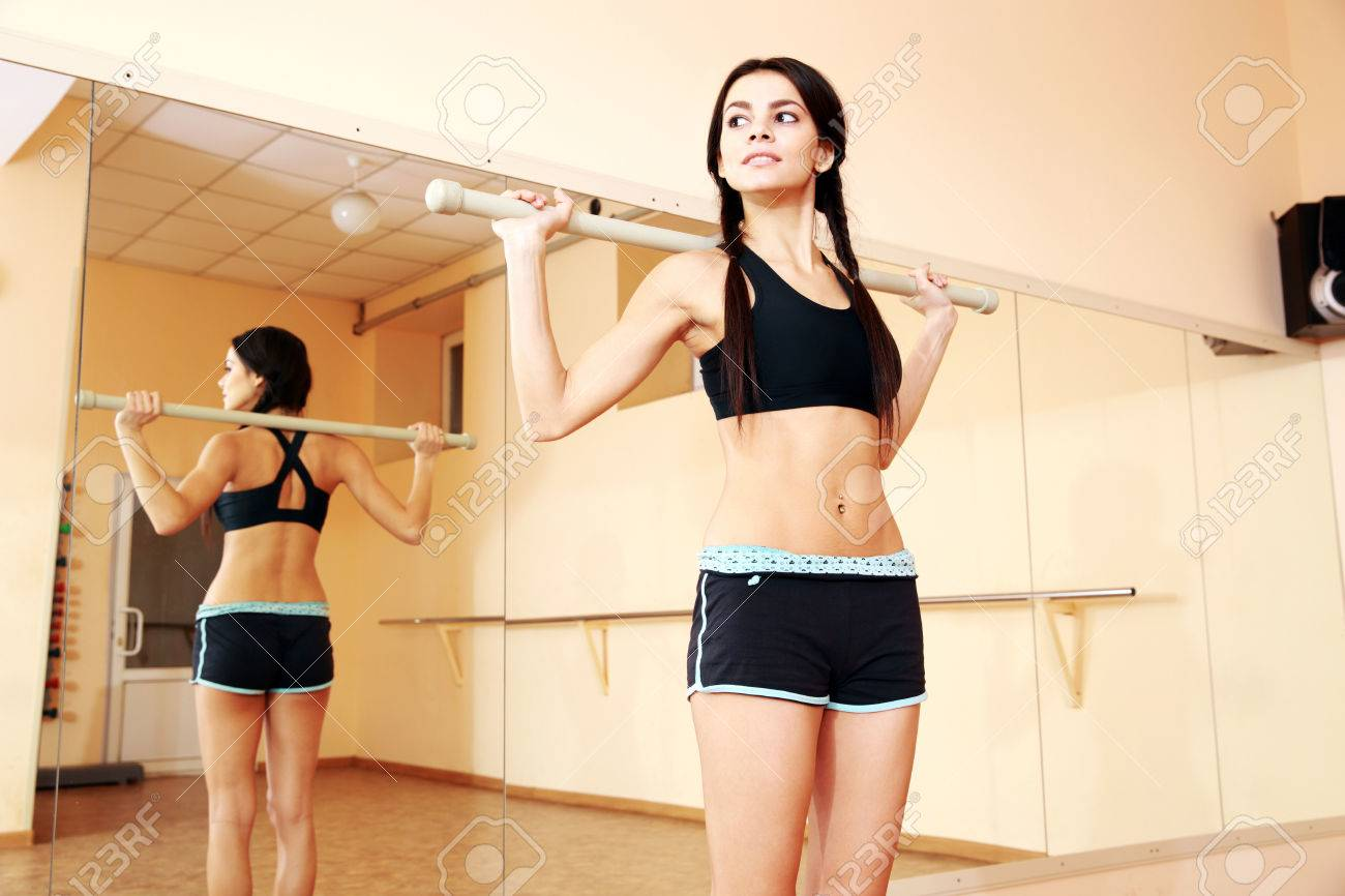Young confident fit woman working out with gymnastic stick at gym Stock Photo - 26554830