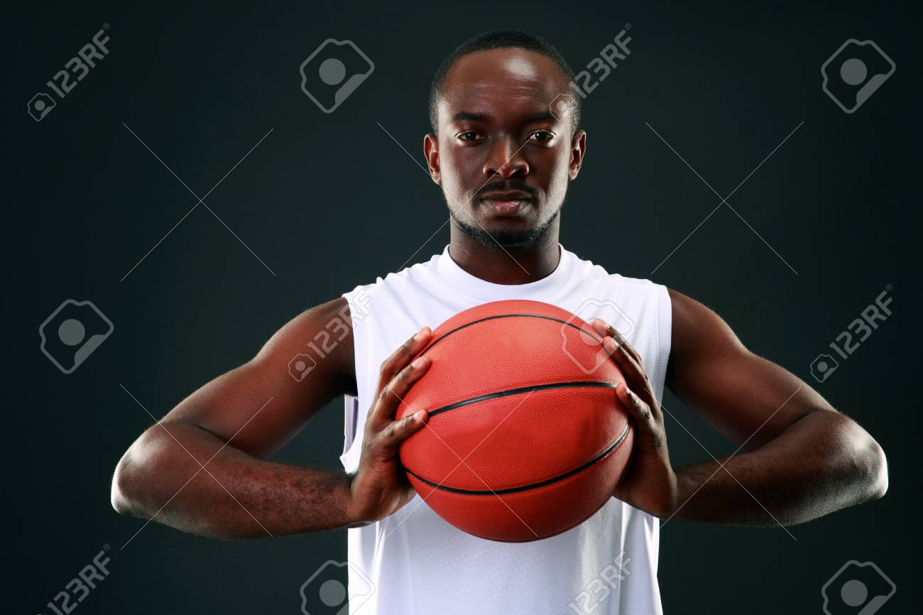 african man holding basketball ball over black background stock