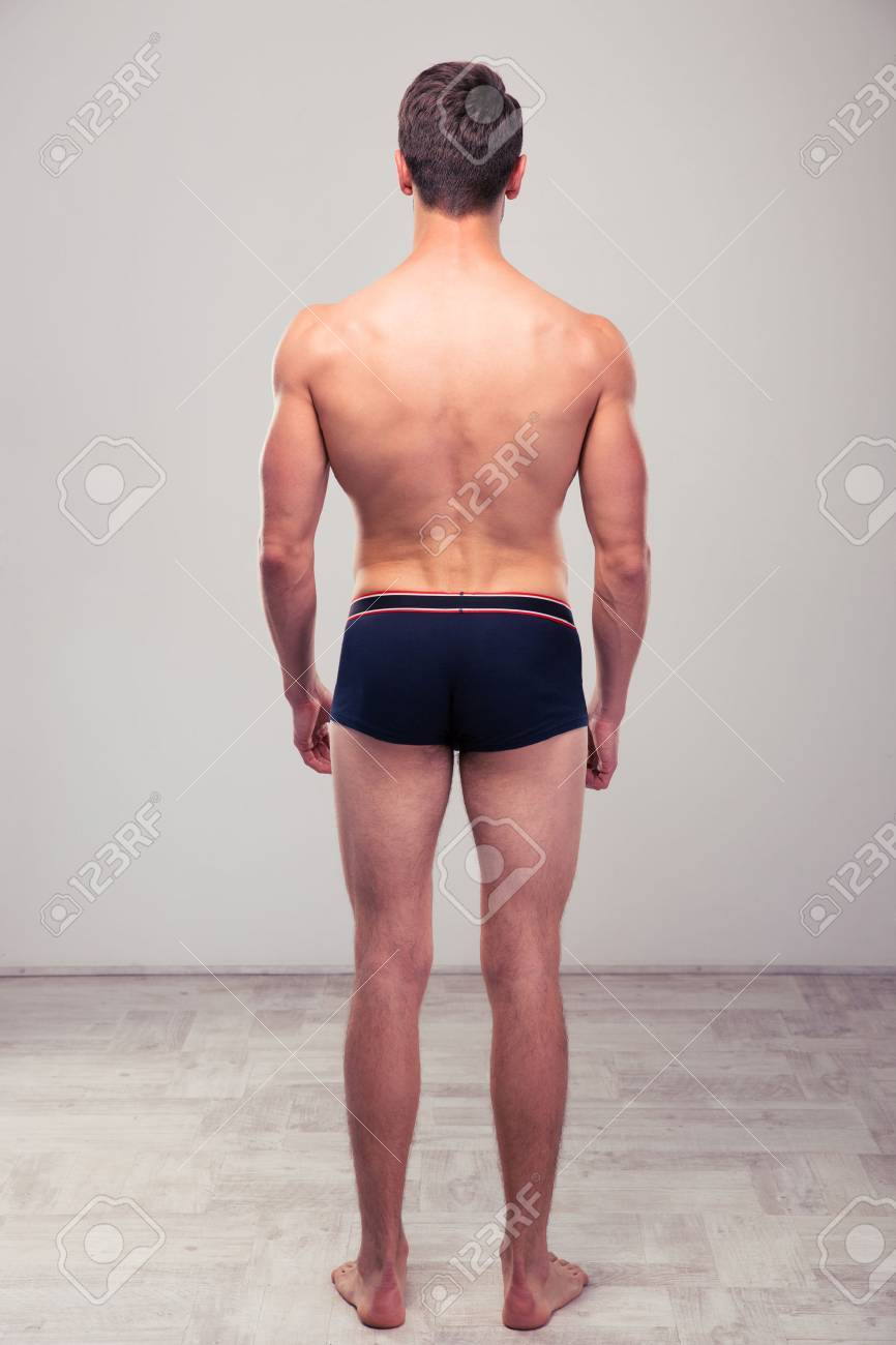 back view portrait of a muscular man standing in studio stock photo