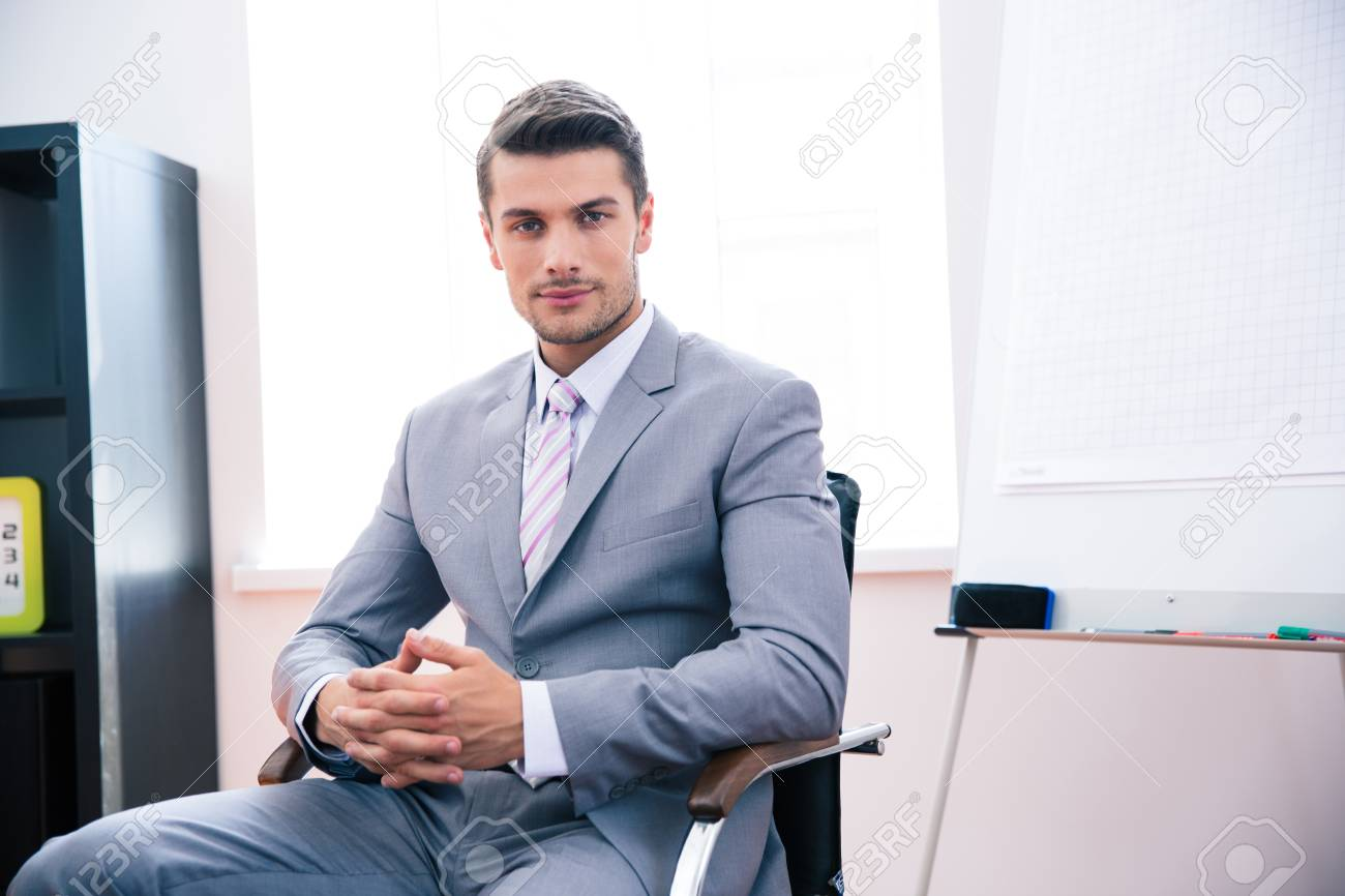 handsome young businessman in suit sitting on the chair in office