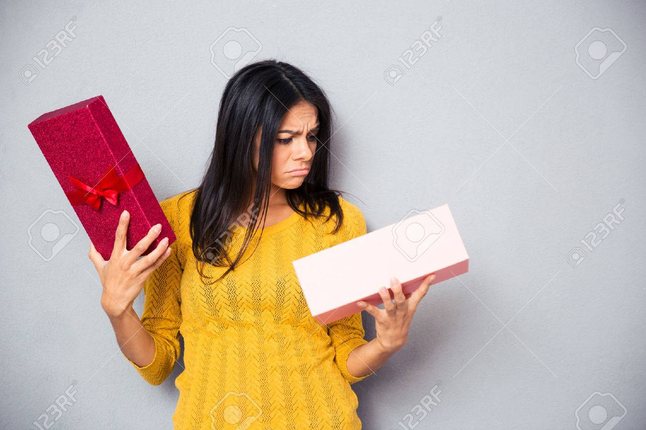 Unhappy young woman holding gift box over gray background - 42455716
