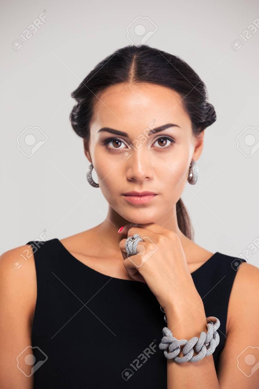 623f2aba14c9 Archivio Fotografico - Concetto di gioielli Ritratto di un modello  femminile di moda in vestito nero che guarda l obbiettivo isolato su uno sfondo  bianco