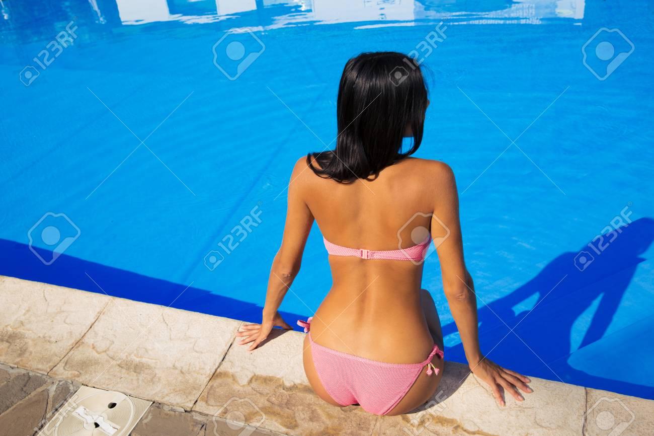 0497823df85f Foto de archivo - Vista trasera retrato de una mujer en bikini sentada  piscina de natación al aire libre cerca de