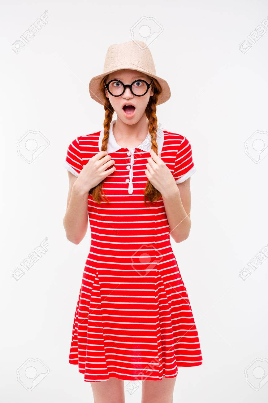 Funny surprised redhead girl with two braids in boonie hat and round  glasses standing over white cb67cb9b679