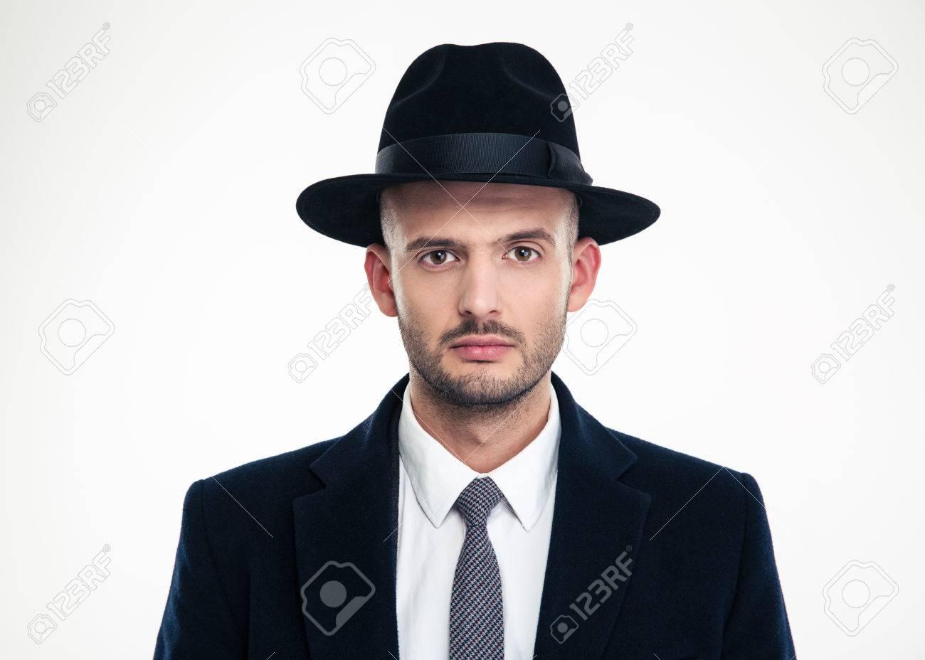 Foto de archivo - Retrato de hombre de negocios joven seus en traje negro y  sombrero mirando a la cámara sobre fondo blanco 40fb97ce559
