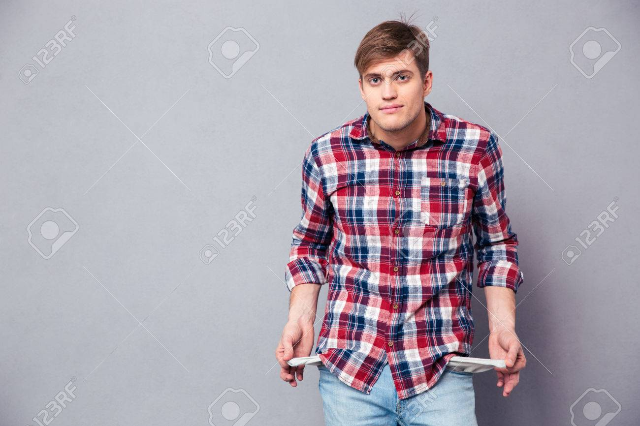 Poor handsome young man in checkered shirt and jeans showing empty pockets over grey background - 50383603