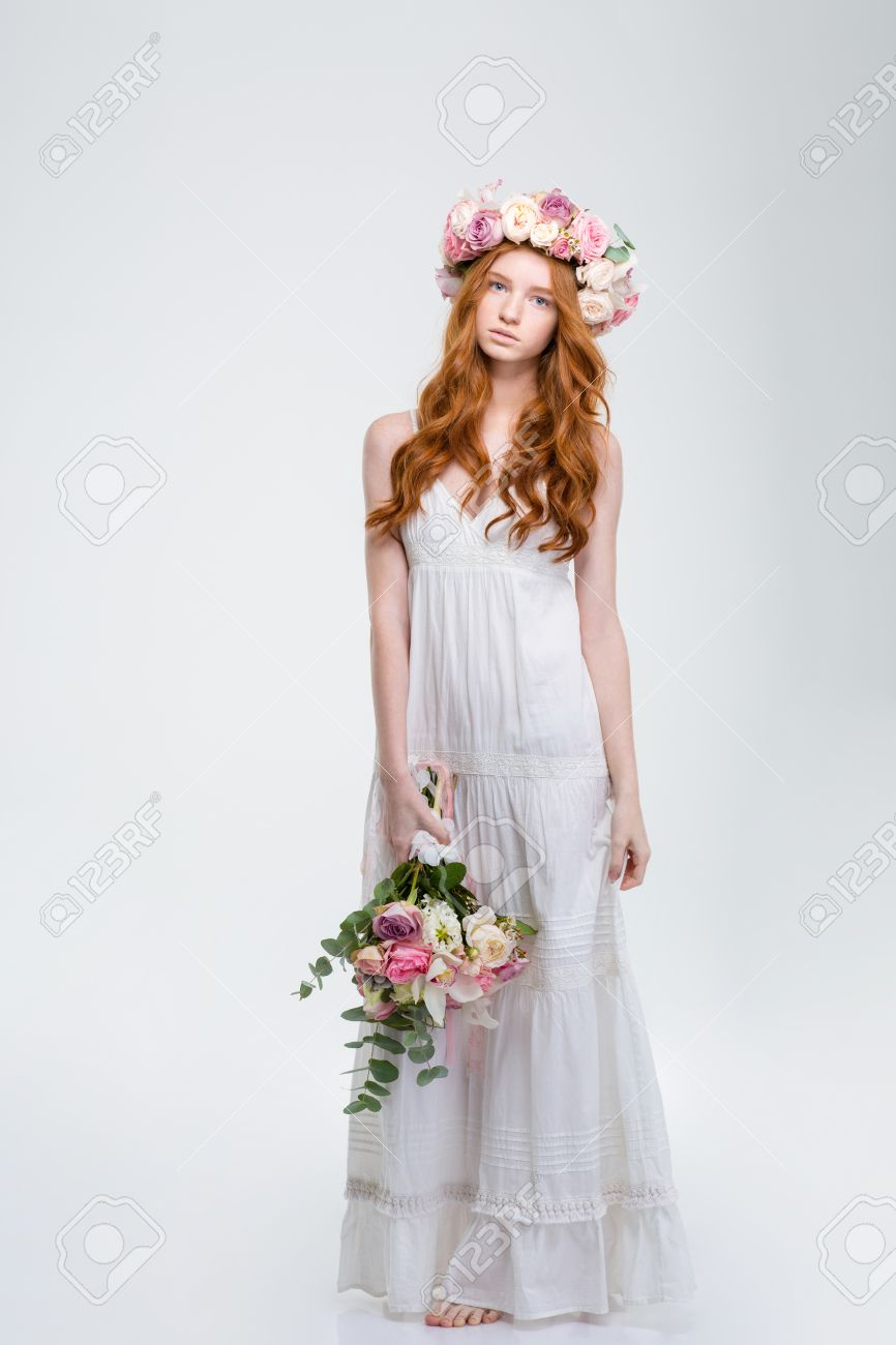 e75883bc56 Full length of beautiful young redhead woman in white sundress and wreath  standing barefoot and holding