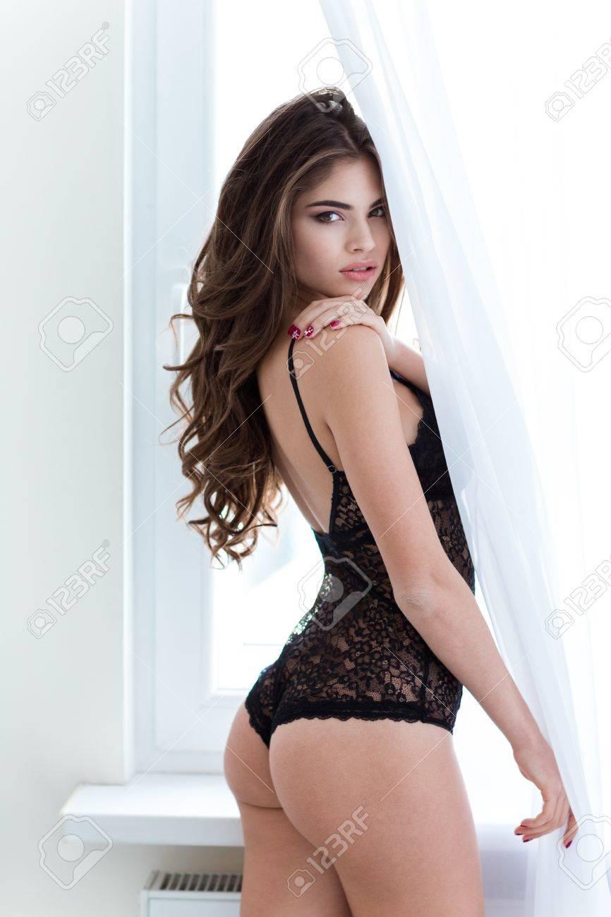 f7c610656 Foto de archivo - Seductora mujer joven sexy en lencería de encaje de pie y  posando cerca de la ventana