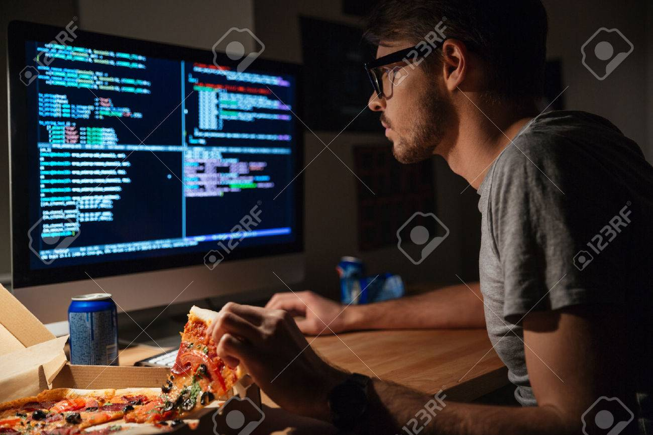 concentrated young software developer eating pizza and coding at home