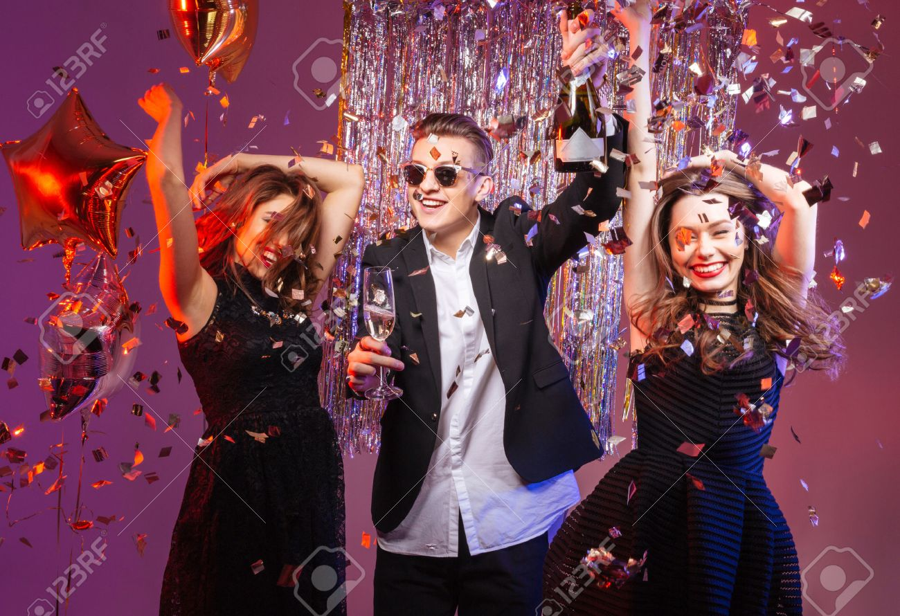 Excited cheerful young friends dancing and having party over purple background - 52249483