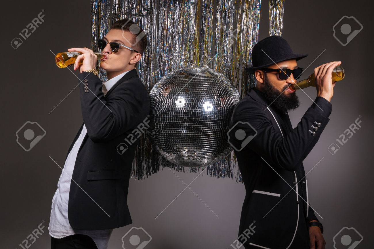 ccc9dd38c4 Stock Photo - Two handsome confident young men in black suits and sunglasses  standing near disco ball and drinking beer over black background