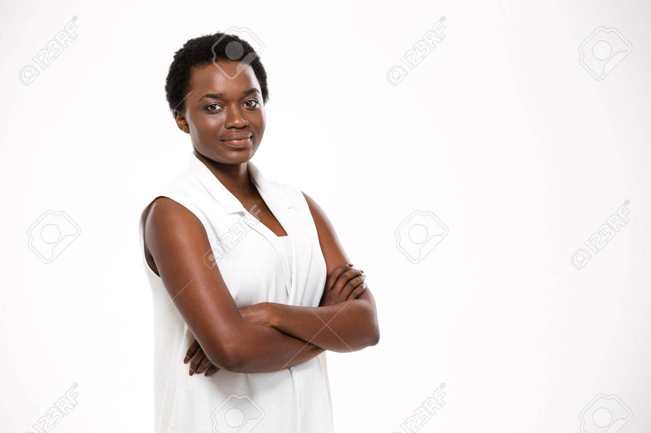 Smiling confident african american young woman standing with arms crossed over white background - 54538073