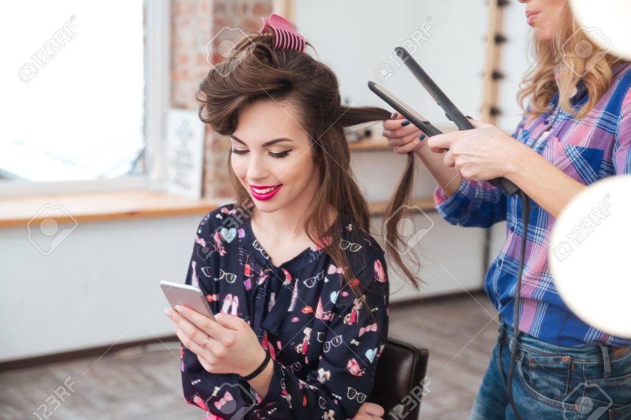 Coiffeur Femme Application Lisseur Pour Cheveux Longs De Jeune Femme Souriante A L Aide Smartphone Dressing Banque D Images Et Photos Libres De Droits Image 53526274