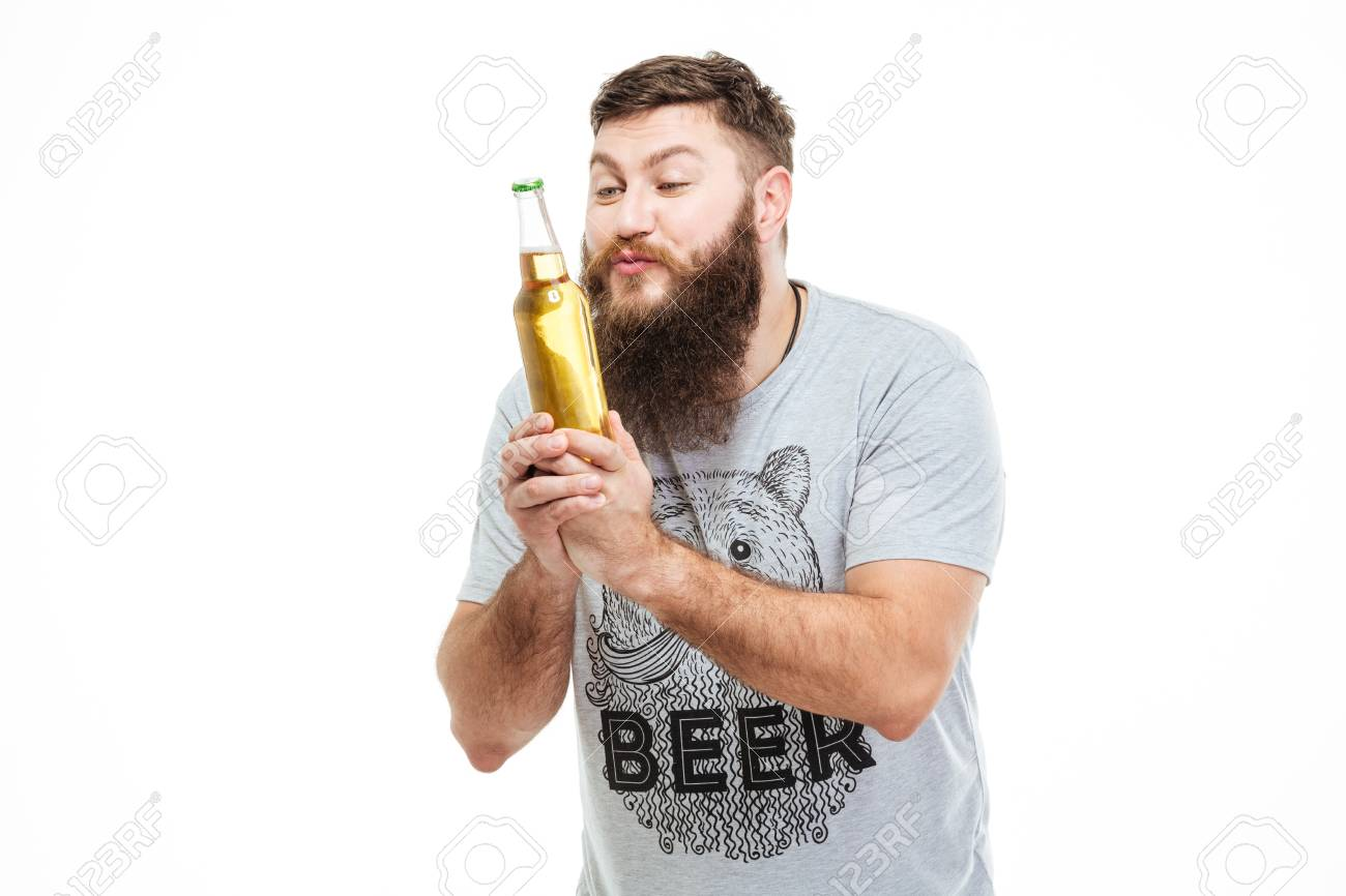 Hansome amusing man with beard holding bottle of beer and looking on it over white background - 53605156