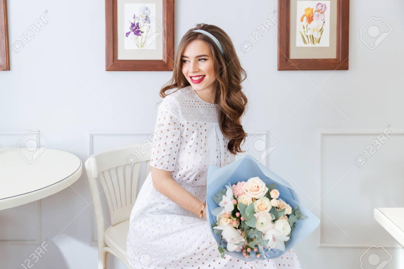 release date 32010 2134f Giovane donna adorabile felice in vestito bianco con il mazzo dei fiori che  si siedono in caffè