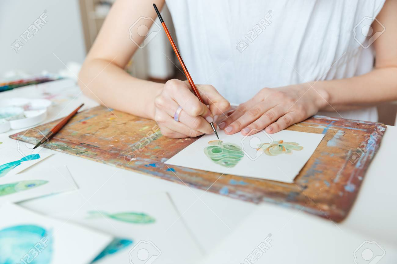 Closeup of hands of woman artist painting with paintbrush and watercolor paints on the table - 55141194