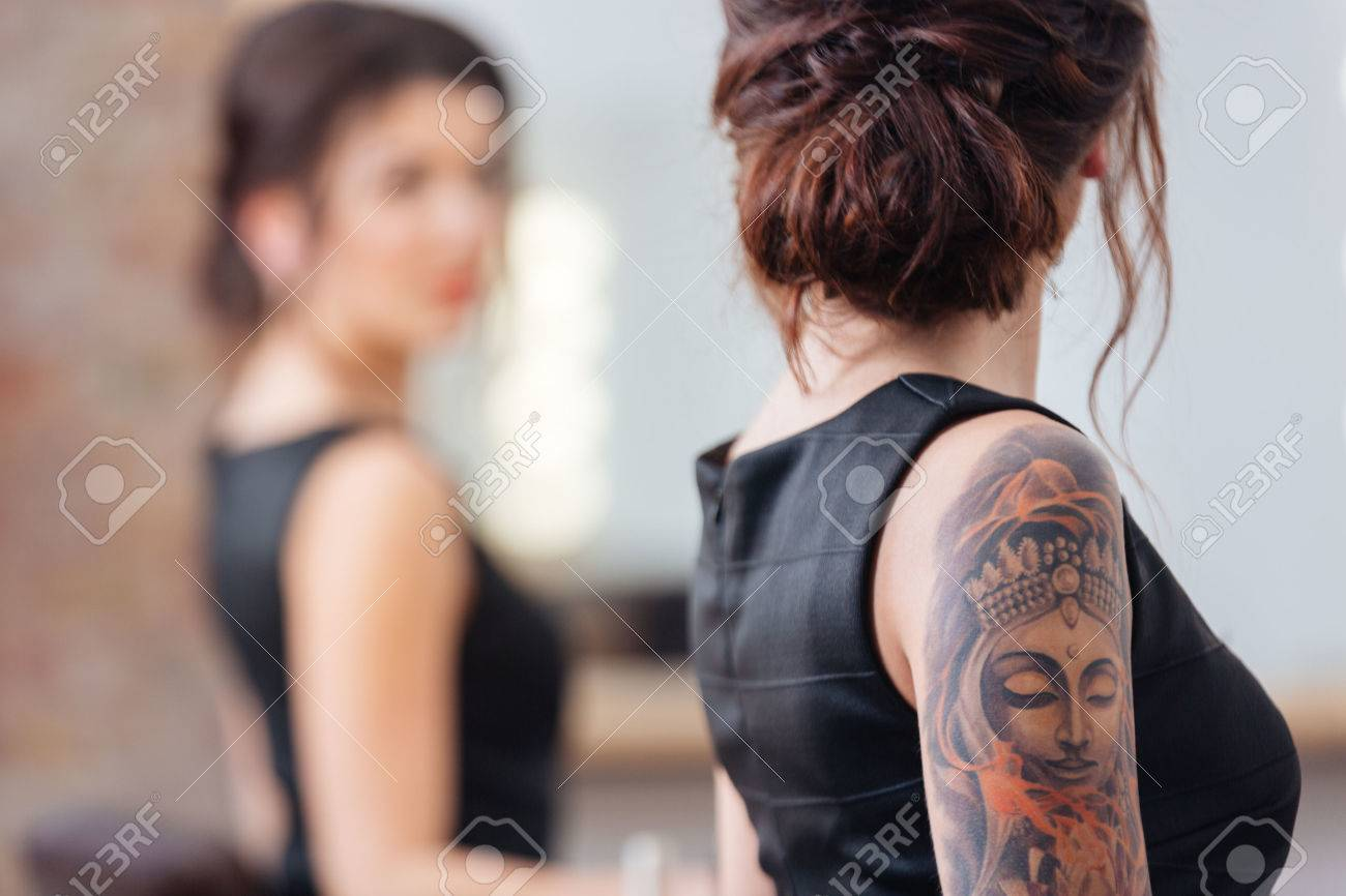 Back view of pretty young woman in black dress with tattoo on her hand standing in front of the mirror - 58212246