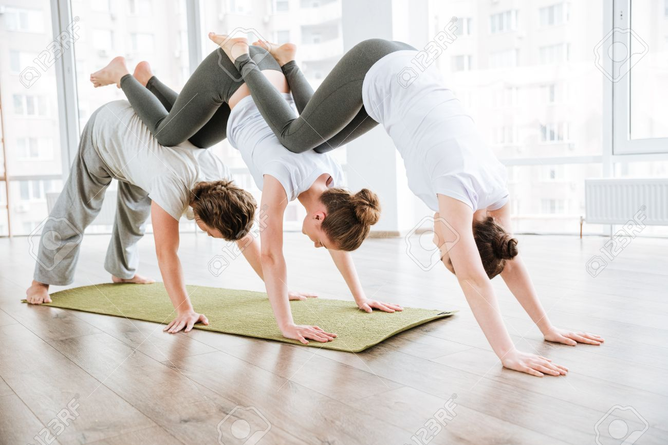 Man And Two Women Practicing Acro Yoga Exercises In Group Together Stock Photo