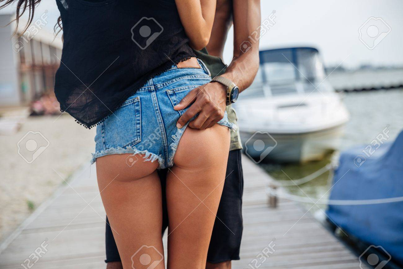 Close up of a male hand on the female ass in jeans shorts outdoors Stock  Photo