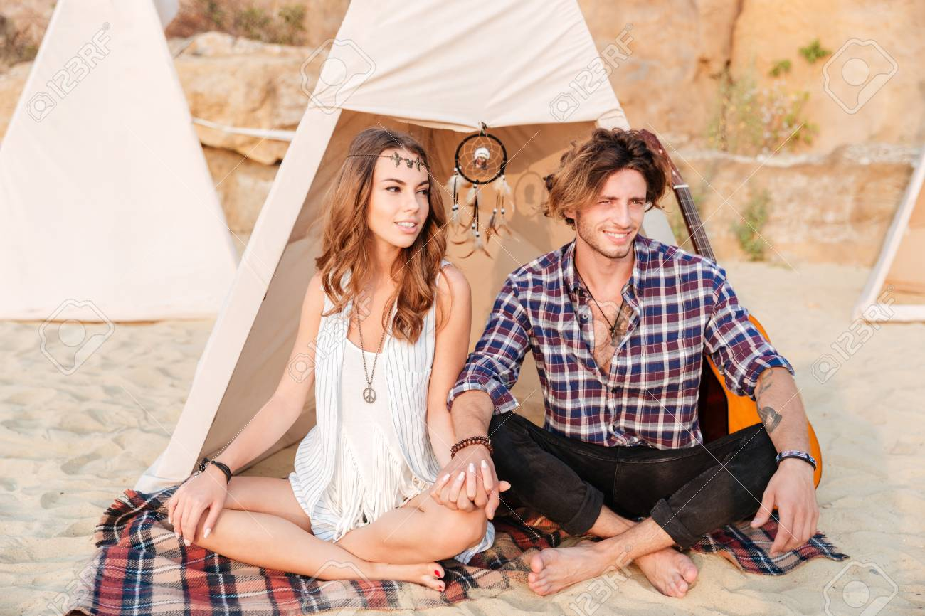 Young Beautiful Smiling Hippie Couple Sitting With Legs Crossed Stock Photo Picture And Royalty Free Image Image 62553596
