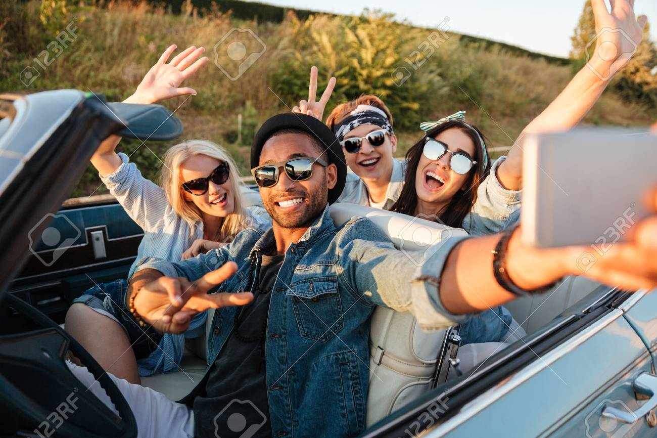 Multiethnic group of happy young people taking selfie with smartphone and showing peace sign in the car - 63163736